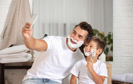 Father and son taking selfie while shaving in bathroom