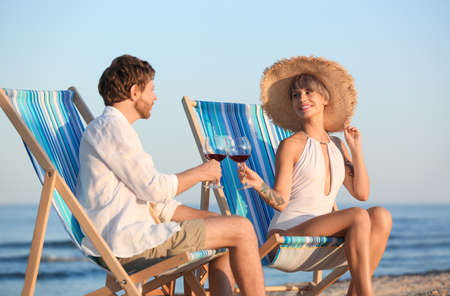 Young couple with glasses of wine in beach chairs at seacoast