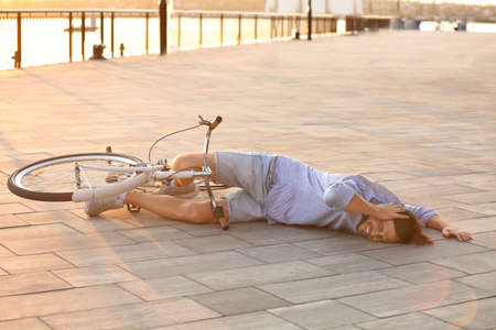 Man fallen off his bicycle on street