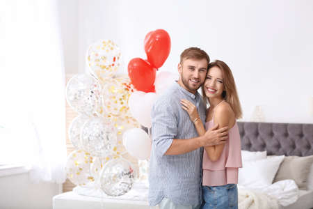 Young couple with air balloons in bedroom. Celebration of Saint Valentines Day Stock Photo