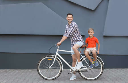 Father and son riding bicycle on street