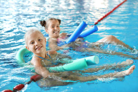Little girls with swimming noodles in indoor pool