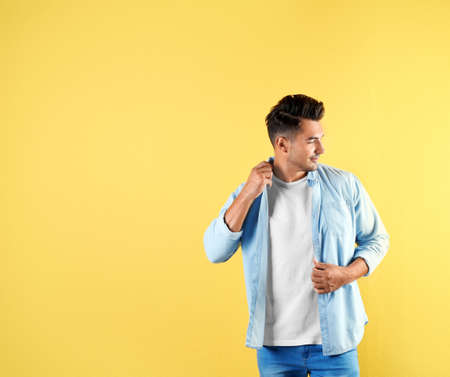 Young man in stylish jeans on color background with space for text Stock Photo