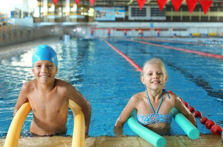 Bambini piccoli con spaghetti di nuoto nella piscina coperta Archivio Fotografico