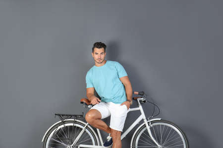 Handsome young hipster man with bicycle on color background