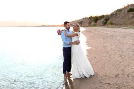 Wedding couple. Bride and groom standing on beach