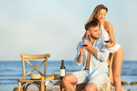 Young couple with glasses of wine having romantic dinner on beach