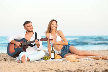 Young couple with guitar having romantic dinner on beach