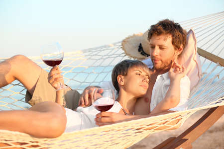 Young couple resting with glasses of wine in hammock on beach