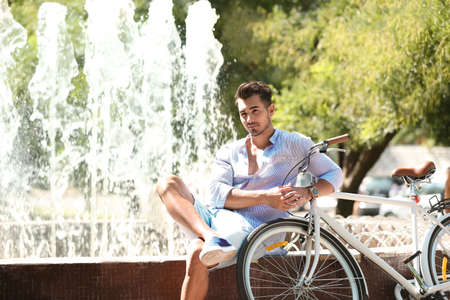 Handsome young hipster man sitting with bicycle near fountain in park Stock Photo