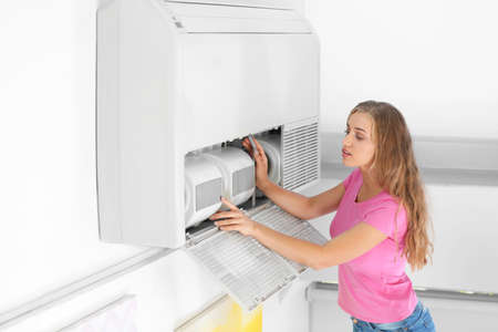 Young woman fixing air conditioner at home Stock Photo