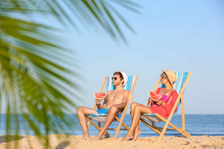Young couple with watermelon slices in beach chairs at seacoast