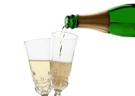 Pouring champagne from bottle into glass on white background