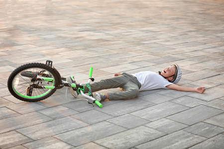 Il ragazzino è caduto dalla sua bicicletta sulla strada
