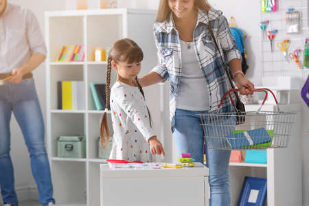Little girl with mother choosing school stationery in store Stock Photo