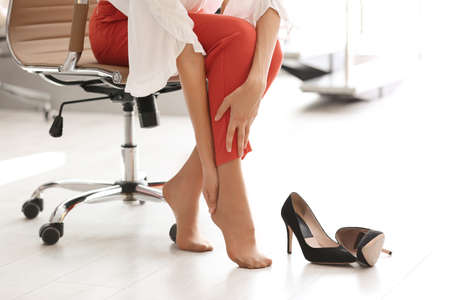 Tired woman taking off shoes at office, closeup view Foto de archivo - 108123126