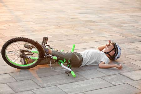 Ragazzino caduto dalla bicicletta per strada Archivio Fotografico