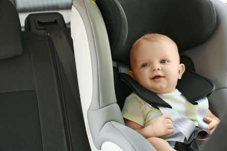 Little baby in child safety seat inside of car