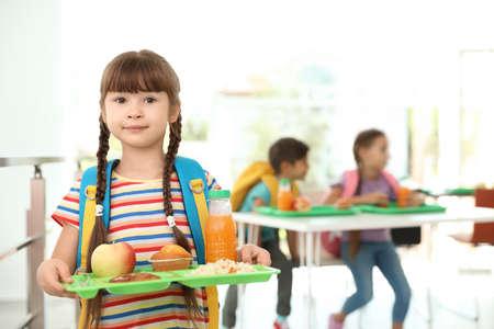 Chica sujetando la bandeja con comida sana en el comedor escolar