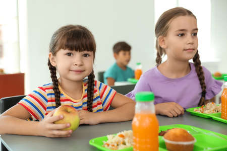 Children sitting at table and eating healthy food during break at school