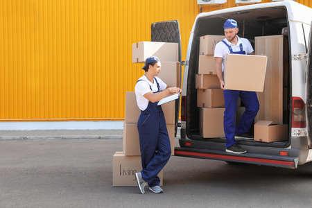 Mudanzas masculinas descargando cajas de van al aire libre