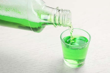 Pouring mouthwash in glass on wooden background. Teeth care