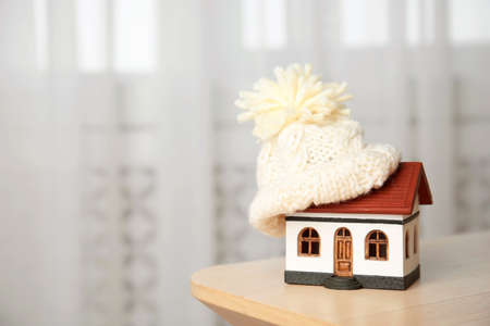 House model with knitted hat on table against blurred background, space for text. Heating concept