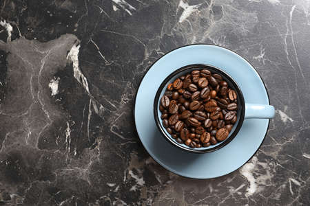 Cup with roasted coffee beans and space for text on grey background, top view