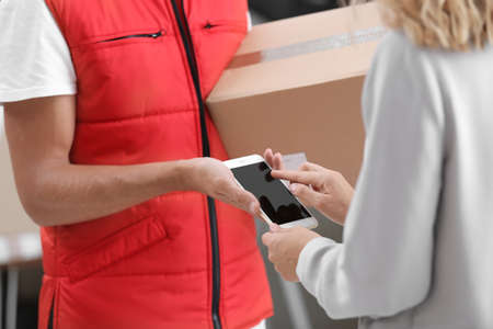 Woman using smartphone app to confirm receipt of parcel from courier, closeup