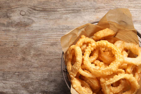 Homemade crunchy fried onion rings in wire basket on wooden background, top view. Space for text