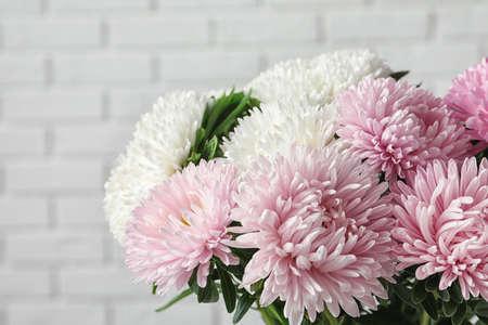 Beautiful aster flower bouquet near brick wall, closeup