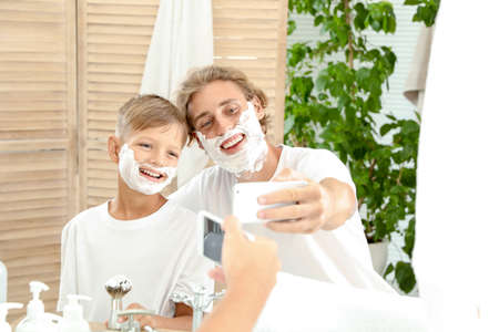 Father and son taking selfie with shaving foam on faces in bathroom
