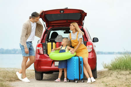 Happy family with suitcases and inflatable ring near car on riverside