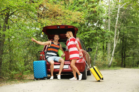 Happy couple near car trunk with suitcases outdoors. Space for text