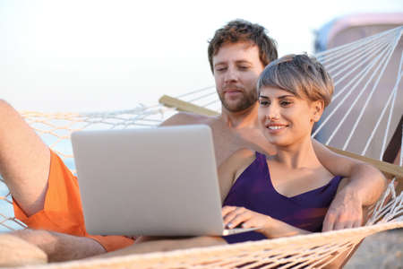 Young couple resting with laptop in hammock on beach Stock Photo