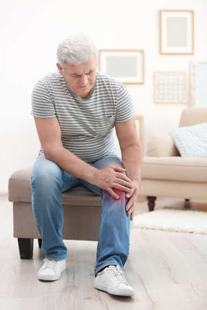 Senior man suffering from knee pain at home Stock Photo