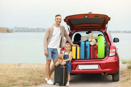 Father and daughter near car trunk with suitcases on riverside. Space for text Stock Photo