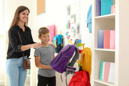 Little boy choosing school supplies with mother in stationery shop