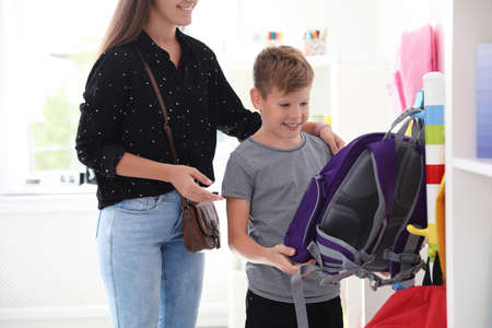 Cute boy with mother choosing backpack in school stationery store Stock Photo
