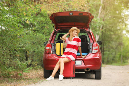 Happy woman sitting in car trunk with suitcases near forest Stock Photo