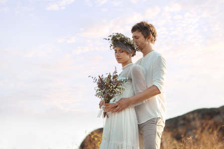 Happy newlyweds with beautiful field bouquet outdoors