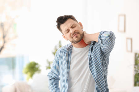 Mature man suffering from neck pain at home Stock Photo