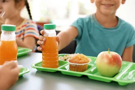 Niños sentados a la mesa y comiendo alimentos saludables durante las vacaciones en la escuela, primer plano