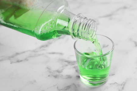 Pouring mouthwash in glass on marble background, closeup. Teeth care