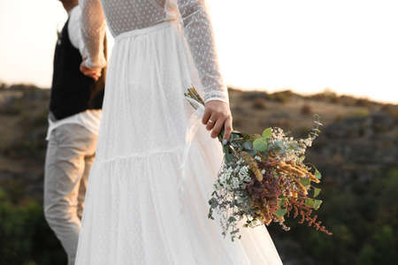 Happy newlyweds with beautiful field bouquet outdoors, closeup Stock Photo
