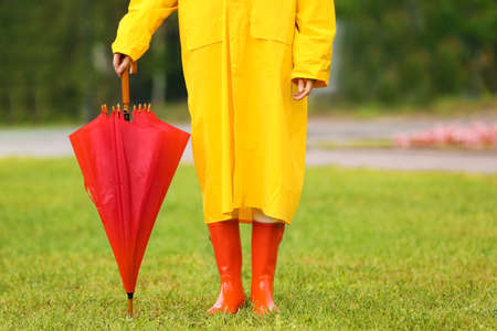 Young woman with red umbrella wearing yellow raincoat in park, closeup Banque d'images