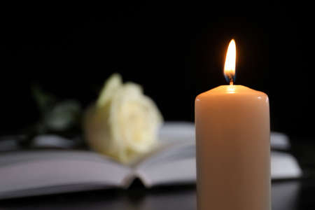 Burning candle on blurred background, space for text. Funeral symbol
