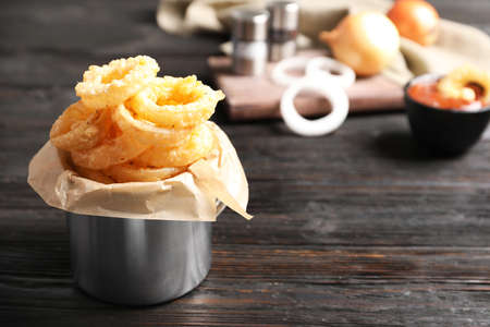 Dishware with homemade crunchy fried onion rings on wooden table. Space for text Stock Photo