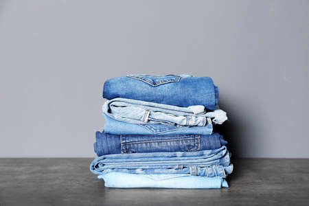 Stack of different jeans on table against gray background