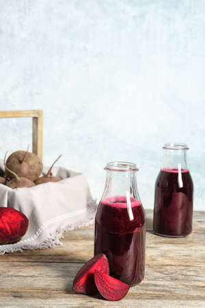 Bottle of beet smoothie on wooden table, space for text